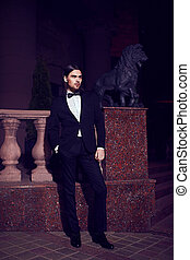 Portrait of fashion elegant long-haired young caucasian sexy muscled attractive handsome man model businessman in black costume with moustache in the street at night