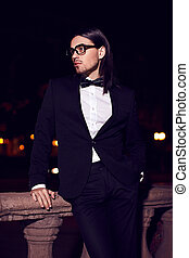Portrait of fashion elegant long-haired young caucasian sexy muscled attractive handsome man model businessman in black costume with moustache in the street at night in glasses