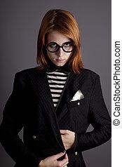 Portrait of fashion girl in jacket and glasses. Studio shot.