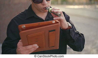 Portrait of fashion man smoking electronic cigarette and using a tablet outdoor
