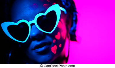 Portrait of fashion model woman with heart shaped glasses in neon light. Fluorescent makeup glowing under UV light. Night club, party, halloween psychedelic concepts.