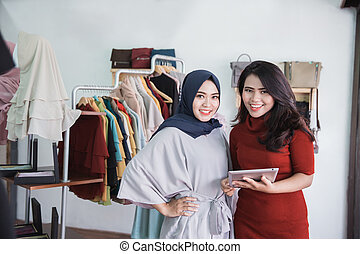 fashion shop owner and her assistant using tablet in fashion sto