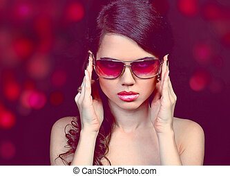 Portrait of fashion young woman in sunglasses isolated on black background