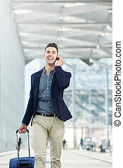 fashionable man on phone call in station with suitcase