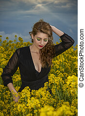 Portrait of fashionable young woman in the yellow flowers field