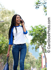 fashionable young woman walking outdoors in the city and talking on mobile phone