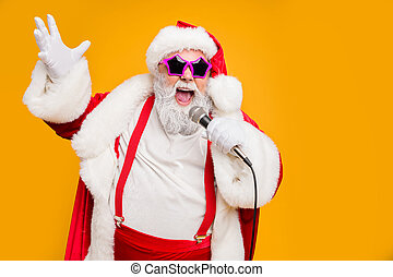 Portrait of fat big belly crazy funky santa claus hold microphones have, live x-mas performance sing carols on christmas night wear red hat headwear trendy suspenders isolated yellow color background