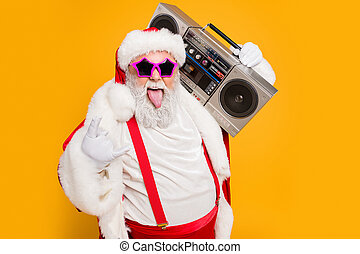 Portrait of fat white hair funny santa claus heavy metal x-mas hipster party hard on noel celebration show horns sign hold retro boombox wear trendy hat suspenders isolated yellow color background