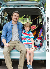 Portrait of father and son sitting in car trunk