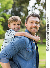Portrait of father carrying boy on back at park