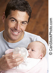 Portrait Of Father Feeding Newborn Baby At Home