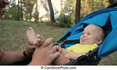Portrait of father kissing baby son's feet