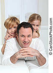 Portrait of father with children up on his back