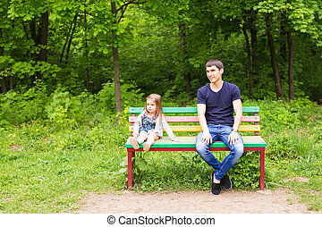 Portrait of father with little baby daughter smiling and sitting on wood bench in summer Park