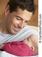 Portrait Of Father With Newborn Baby At Home