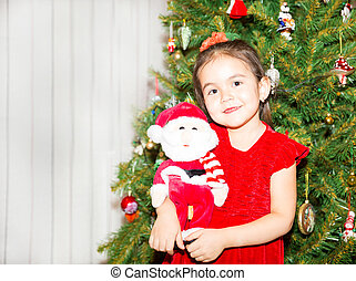 Portrait of fazakh, asian child girl around a Christmas tree decorated. Kid on holiday new year