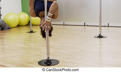 Portrait of female african dancer who is turning around the pole upside-down. Yound professional in blue sportswear is holding the metal equipment by her hands with silver armlets and finger rings on. Beautiful lady has a dance training in modern bright studio woth wooden floor and yellow balls on ...