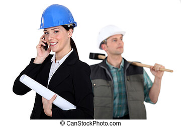 portrait of female architect making a call and carpenter in background