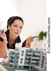 Portrait of female architect with architectural model