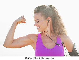 Portrait of female athlete showing biceps outdoors