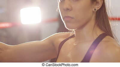 Portrait of female boxer with her arm on the punching bag -...