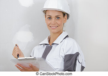 portrait of female builder holding clipboard