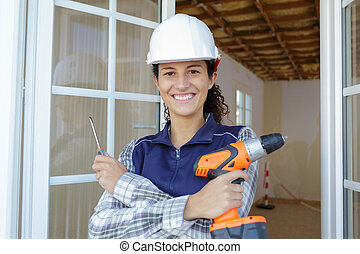 portrait of female builder holding screwdriver and cordless...