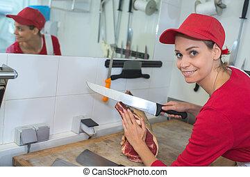 portrait of female butcher cutting meat