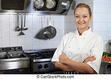 Portrait Of Female Chef Standing In Kitchen