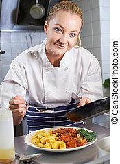 Portrait Of Female Chef Working In Restaurant Kitchen
