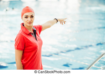 Portrait of female coach with a stop watch and clipboard by pool at leisure center