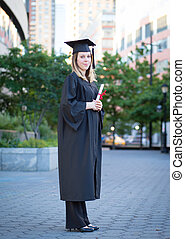 Portrait of female college student in graduation cap and gown holding diploma on campus