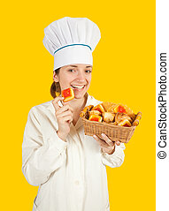 Portrait of female cook with sweets over yellow background
