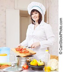 cook with tomatoes on cutting board at kitchen