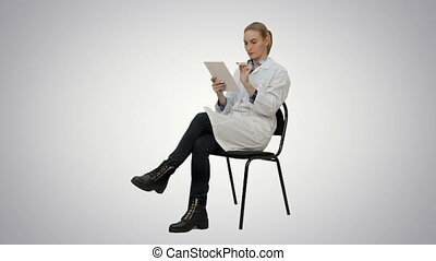 Portrait of female doctor with tablet computer reading medical report on white background.