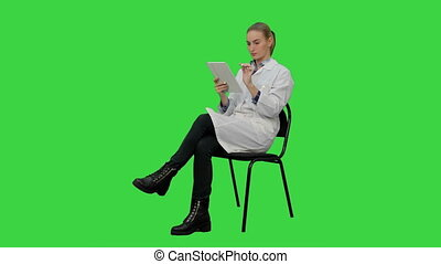Portrait of female doctor with tablet computer reading medical report on a Green Screen, Chroma Key.