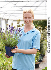 Portrait Of Female Employee At Garden Center Holding Plant