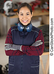 portrait of female engineer in workshop with arms crossed