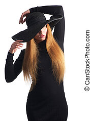 Portrait of female fashion model posing in black hat