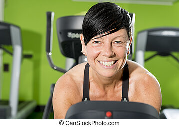 Portrait of Female Fitness Trainer on a Cardio Machine in Gym