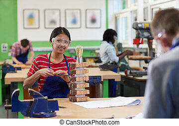 Portrait Of Female High School Student Making Lamp In Woodwork Lesson