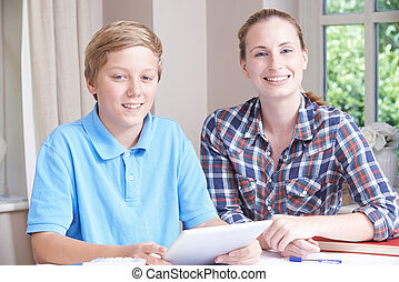 Portrait Of Female Home Tutor Helping Boy With Studies Using Digital Tablet