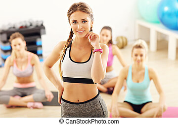 Portrait of female instructor with her group in gym
