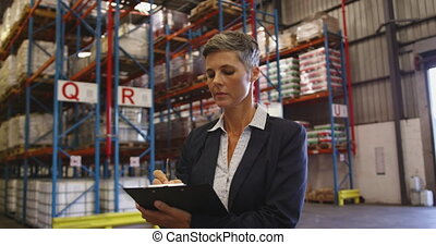 Portrait of female manager smiling to camera in a warehouse ...
