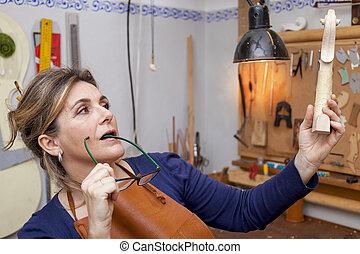 portrait of female mature violin maker while testing the...