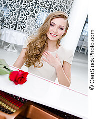 Portrait of female musician with red rose playing piano