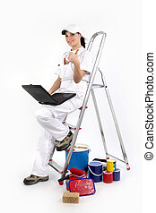 portrait of female painter decorator with laptop leaning against ladder