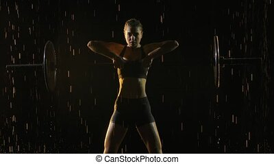 Portrait of Female performing deadlift exercise with weight bar. Confident young woman doing weight lifting workout barbell at crossfit gym. Shot in a dark studio in the rain and staged light. Black background. Slow motion. Close up.