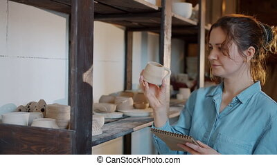 Portrait of female potter checking ceramics and writing ...
