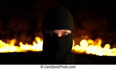 Portrait of female protesting activist in black balaclava...